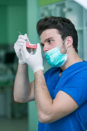 palate: Dental prosthesis, dentures, prosthetics work. Prosthetics hands while working on the denture, false teeth, a study and a table with dental tools.