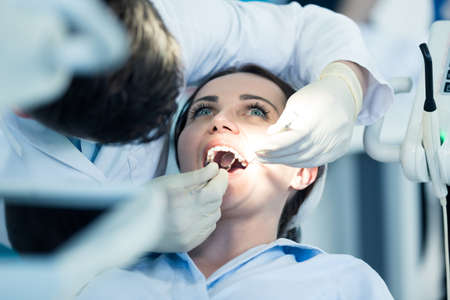 Dentist examining Patient teeth with a Mouth Mirror. Dentist is a Man, Patient is a Woman. Patient is Relaxed and not scared of Dentist. Banco de Imagens