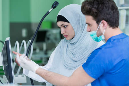 Dental prosthesis, dentures, prosthetics work. Arab students with hijab while working on the denture, false teeth, a study and a table with dental tools