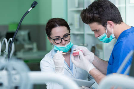 치과 보철, 틀니, 보철물 작업. 보철물은 의치, 틀린 치아, 연구 및 치과 도구가있는 테이블에서 작업하면서 손에 넣습니다.