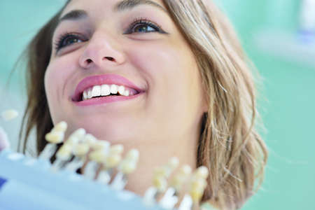 A pretty young woman with a bright, white smile lying in the dentists chair having a checkup Stock Photo