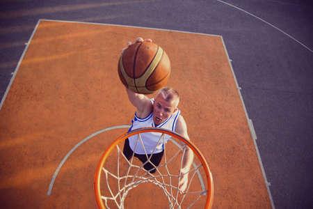 Basketball street player making a slam dunk