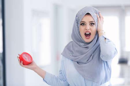 Beautiful Arab businesswoman shock at deadline clock in office.