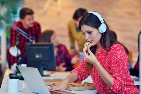 Vrolijke kantoor meisje genieten van pizza tijdens de lunch