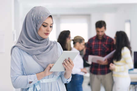 headcloth: Arabic business woman working in team with her colleagues at office