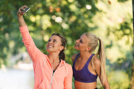 Beautiful girls taking a selfie with a smart phone before going for a run outdoors. Stock Photo