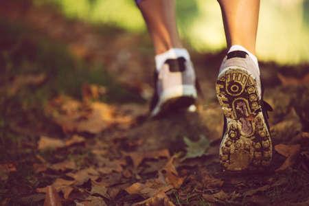 Vrouw voeten in schoenen op een bospad op zonsondergang.