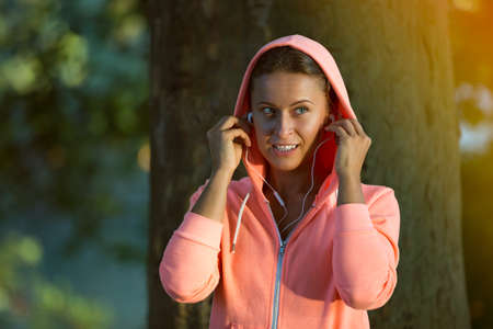 radio activity: Beautiful woman during fitness at park is listening music. Stock Photo