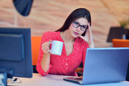 brown haired: Beautiful classy brown haired businesswoman enjoying coffee in bright office. Stock Photo