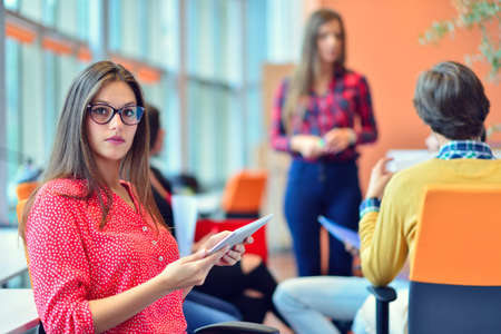 Young people meeting with digital tablet in startup office. Stock Photo