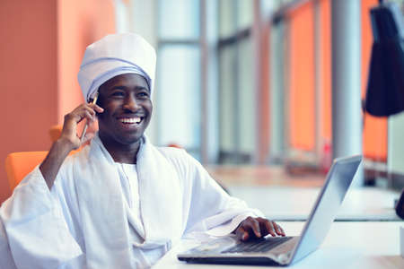 Sudanese business man in traditional outfit using mobile phone in office. Stock Photo