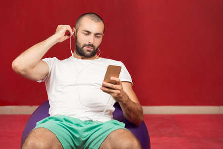 swiss ball: man sitting on a gym ball holding a phone after doing a work out.