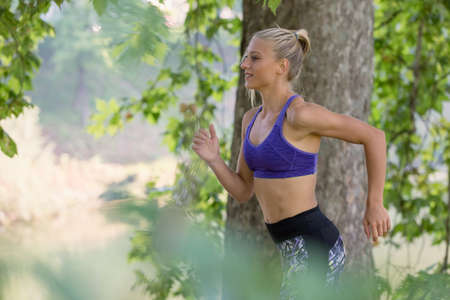 Jogging woman running in park in sunshine on beautiful summer day. Sport fitness model of Caucasian ethnicity training outdoor for marathon. Stock Photo