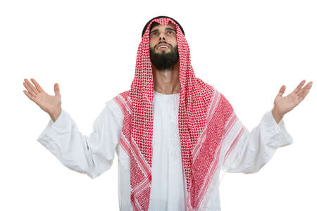 Young arab man of muslim religion praying isolated on white background.