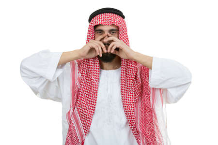 sheik: Young disappointed Arab with a checkered veiland holding his head isolated on white background