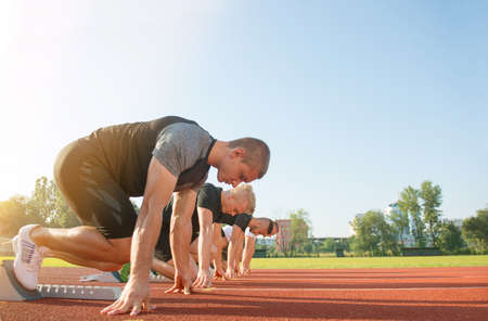 Close-up side view of cropped people ready to race on track field.