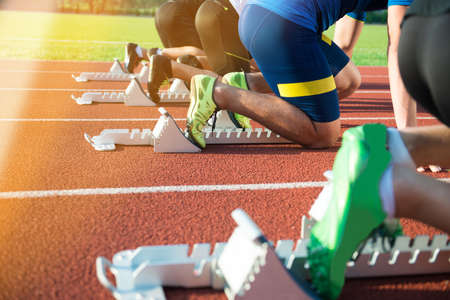 春のスタートの準備ができて開始ブロックに足。太陽フレアとスタジアムでレースを開始しようとしてのスポーツ選手の足に焦点を当てます。