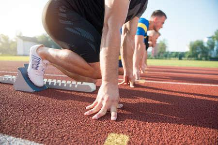 Primer plano vista lateral de la gente recortadas listos para correr en campo de la pista. Foto de archivo