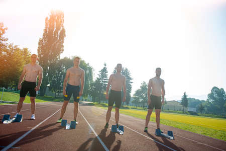 Male athletics runners on starting line without shirts Reklamní fotografie