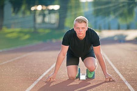 Atletische man op de rails begint te lopen. Gezonde fitness concept met een actieve levensstijl
