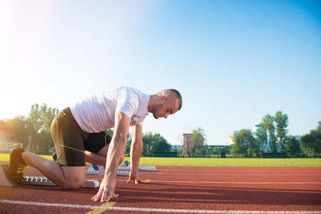 starting position: Male athlete on starting position at athletics running track. Runner practicing his sprint start in athletics stadium racetrack.