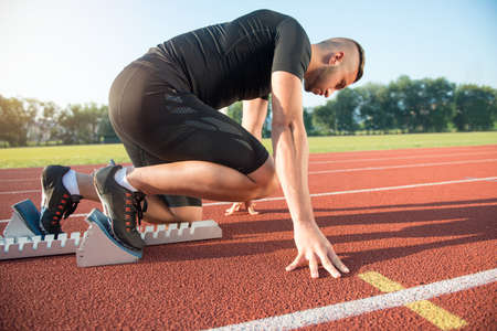 racetrack: Male athlete on starting position at athletics running track. Runner practicing his sprint start in athletics stadium racetrack.