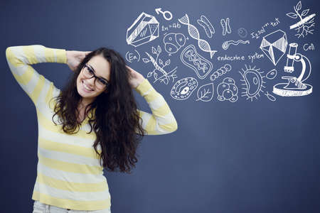 science symbols metaphors: Young smiling woman on blue gray background with biology icons.