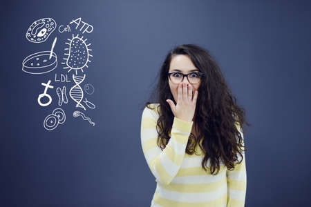 science symbols metaphors: Young amazed woman on blue gray background with biology icons.