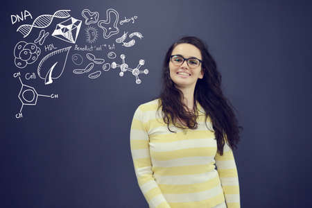 science symbols metaphors: Young smiling woman on blue gray background with universum icons. Confusion.