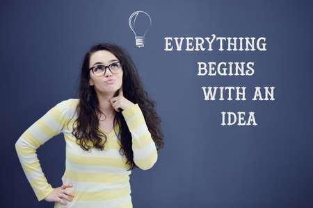 predicament: Young thinkful woman on blue gray background with idea sign. Confusion. Predicament. Financial and business concept.