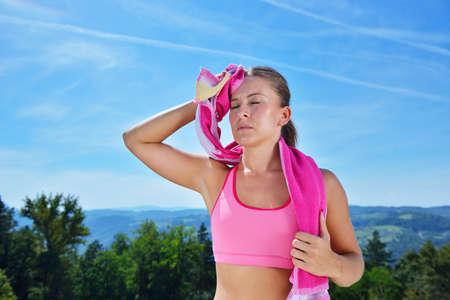 Sudato fitness donna stanca dopo l'allenamento. Caucasica atleta sudorazione femminile ed esausto dopo l'allenamento sul fondo cielo copia spazio.