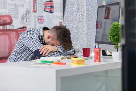 slacker: Tired overworked businessman sleeping over a laptop in a desk at job in his office. Stock Photo