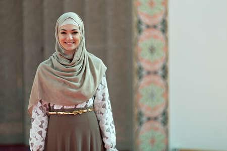 Joven y bella mujer musulmán que ruega en la mezquita.