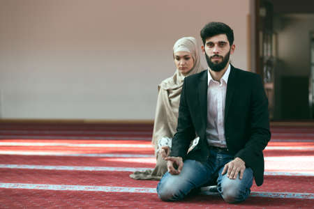 familia orando: el hombre y la mujer musulmana rezando en la mezquita. Foto de archivo