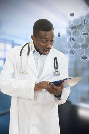 African American doctor shocked and scared by information on a clipboard Stock Photo