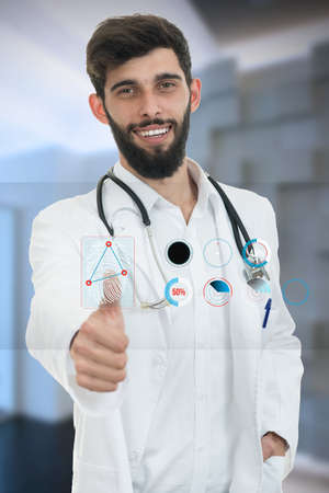 friendly male doctor showing thumbs up in hospital. Stock Photo