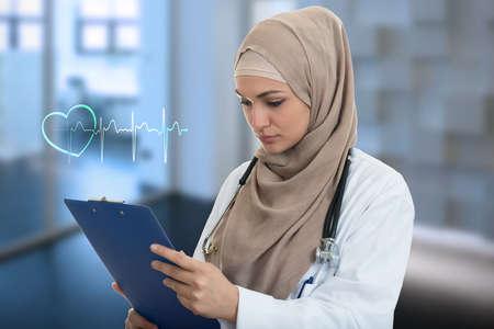 Close-up portret van vriendelijke, glimlachende vertrouwen moslim vrouwelijke arts die map zorgverlener.