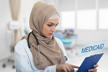portrait of worried muslim female Medical doctor holding paperclip in hospital. Medicaid sign