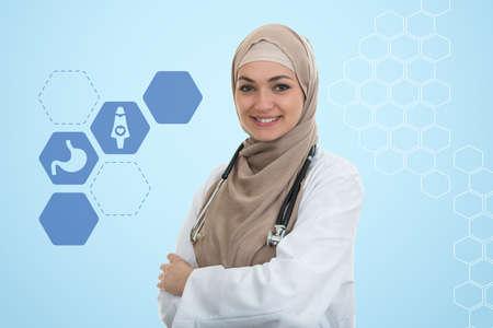 close up portrait of arab female doctor smiling while using stethoscope. Stock Photo