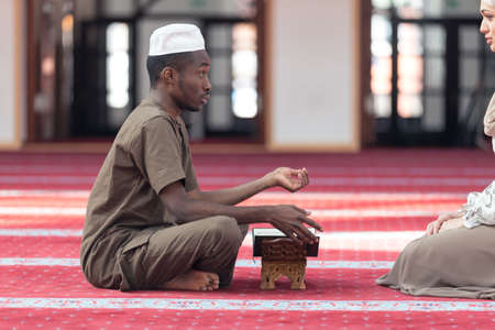 Black Muslim man and woman praying in mosque.