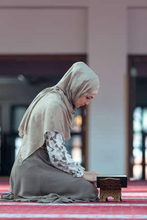 sufi: Young muslim woman reading koran in mosque.