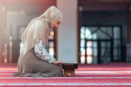 Jonge moslimvrouw het lezen koran in de moskee.