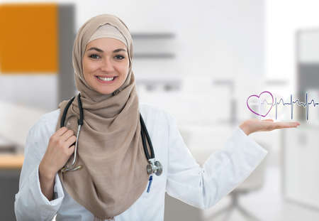 Closeup portrait of friendly, smiling confident Muslim female doctor holding EKG sign in modern hospital Фото со стока