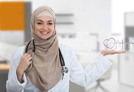 Closeup portrait of friendly, smiling confident Muslim female doctor holding EKG sign in modern hospital Standard-Bild