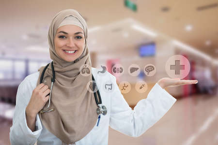 Closeup portrait of friendly, smiling confident Muslim female doctor holding medical symbols in modern hospital
