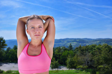 Young sports woman stretching her arms up while exercising on a mountain with a blue sky. Stock Photo