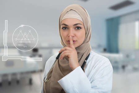 shh: Closeup portrait of friendly, confident muslim with hijab doctor showing shh sigh, silence, healthcare professional in modern hospital
