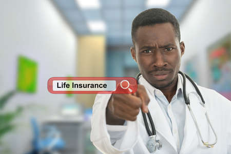 Angry african black male doctor pointing finger at you with stethoscope around his neck. Life insurance search. Stock Photo