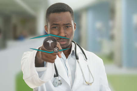 Angry african black male doctor pointing finger at you with stethoscope around his neck, pointing at camera with serious face and medical symbols. Stock Photo