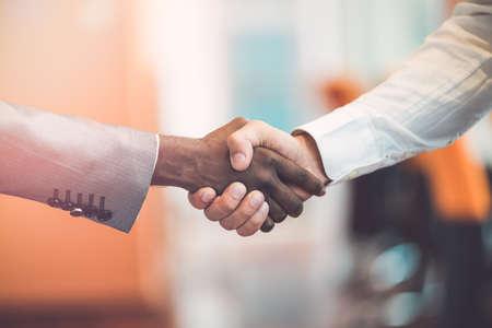 racismo: Handshake between african and a caucasian man